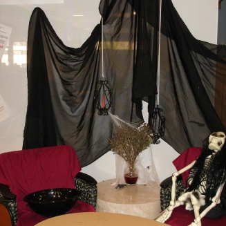 Skeleton in one chair, empty chair for user to sit next to. Decorated for Halloween
